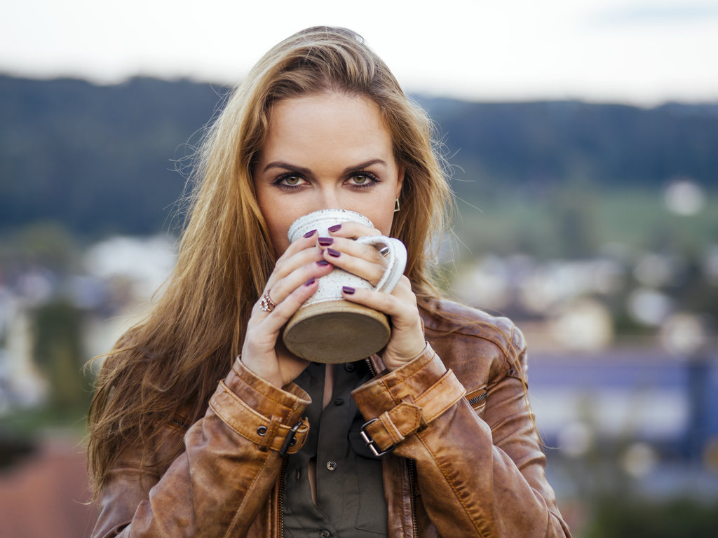 Beautiful brunette woman enjoying coffee outside